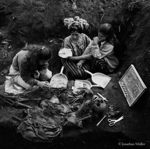 Two sisters watch as the remains of their mother and four small siblings are exhumed, Nebaj, Quiche, Guatemala (2000) - Photograph by Jonathan Moller, courtesy of the Historical Memory Project