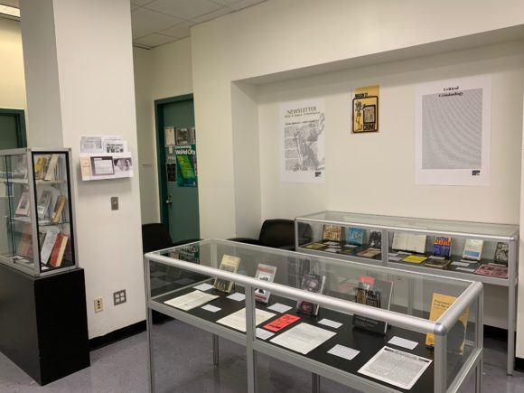 Glass cases filled with materials depicting the history of critical criminology at John Jay College