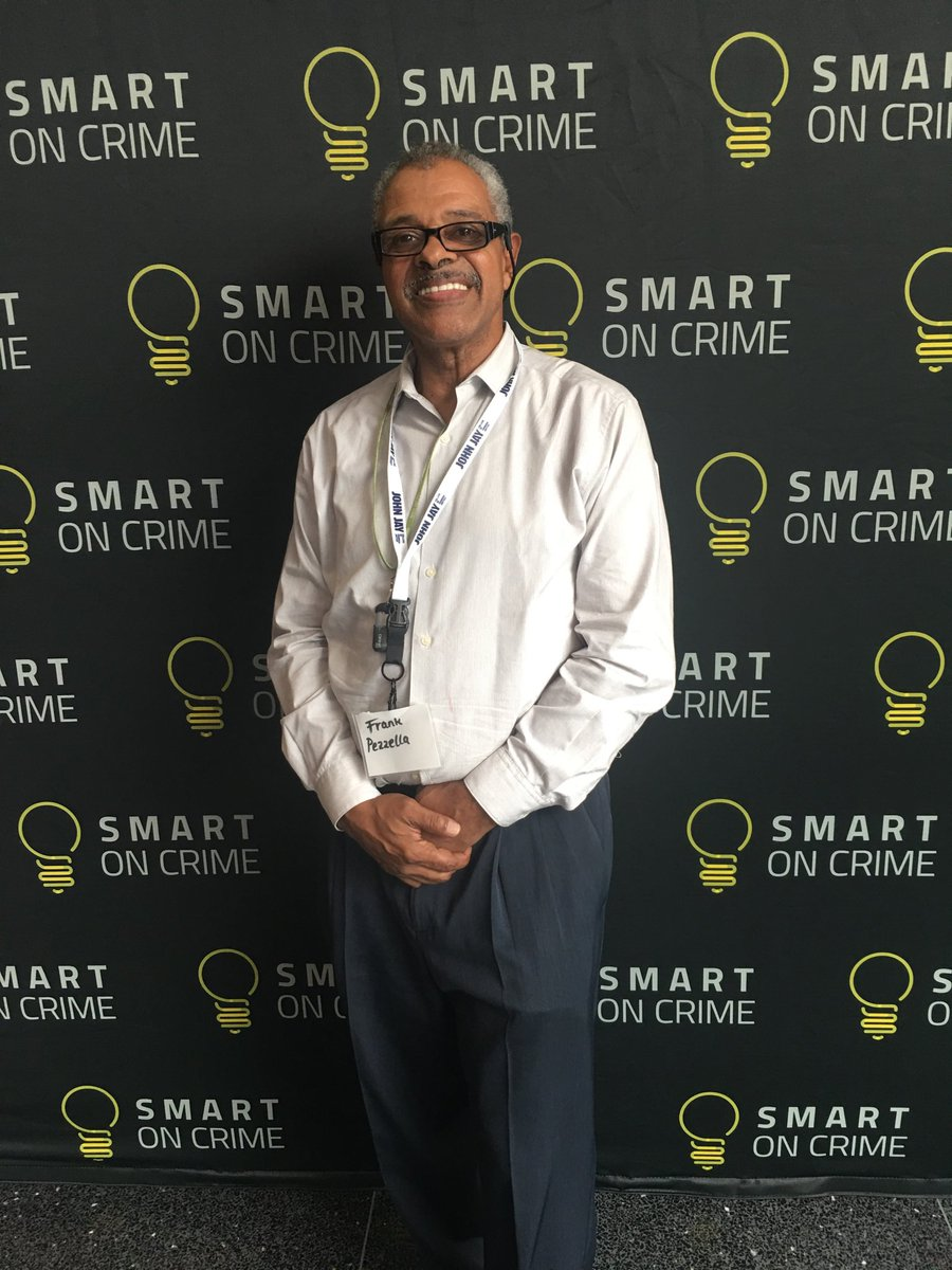 "Frank Pezzella stands in front of a step-and-repeat that reads ""Smart on Crime,"" he is visible to the knee and holding his hands clasped in front of his body"